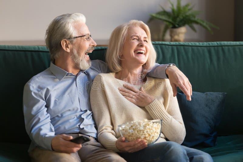Coppie, uomo e donna invecchiati di risata guardanti TV e mangianti popcorn fotografia stock libera da diritti