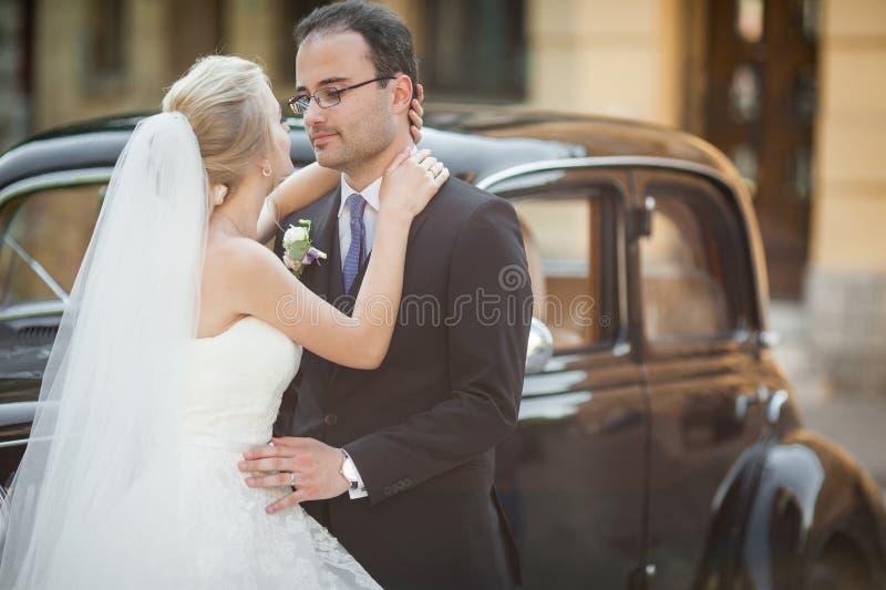 Coppie, uomo felice e moglie della persona appena sposata abbraccianti vicino alla retro c alla moda immagine stock libera da diritti
