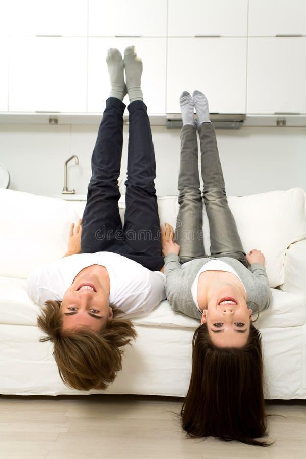 Coppie upside-down sul sofà fotografie stock libere da diritti