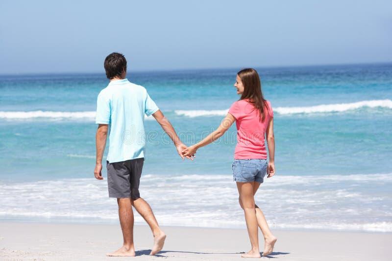 Coppie in vacanza che cammina lungo la spiaggia di Sandy fotografie stock libere da diritti