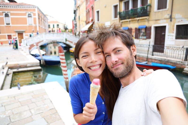 Coppie a Venezia, mangiante il gelato che prende selfie fotografia stock libera da diritti