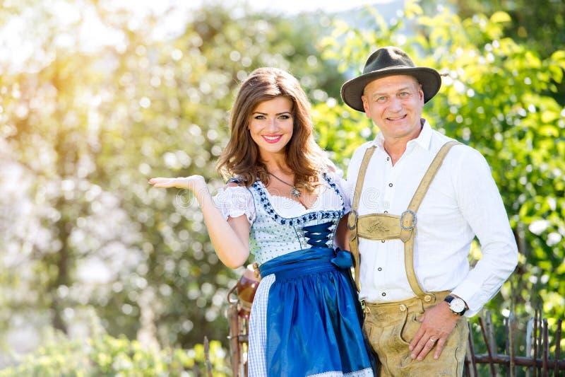 Coppie in vestiti bavaresi tradizionali che stanno nel giardino fotografie stock
