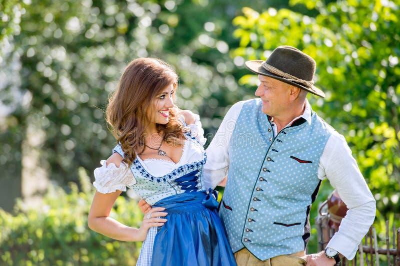 Coppie in vestiti bavaresi tradizionali che stanno nel giardino immagini stock libere da diritti