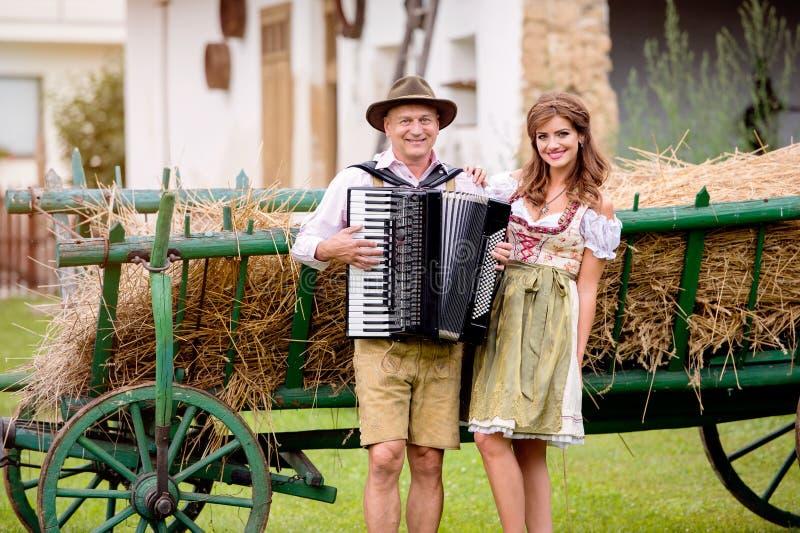 Coppie in vestiti bavaresi tradizionali con la fisarmonica, vagone del fieno fotografie stock