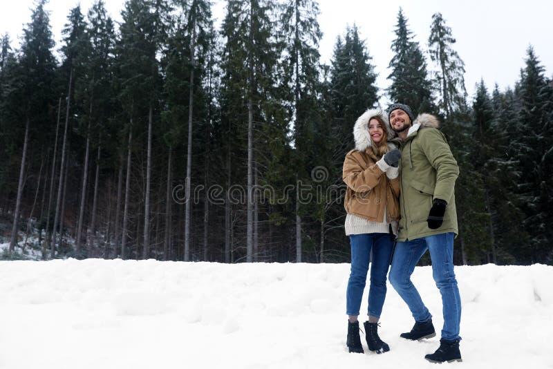 Coppie vicino alla foresta della conifera il giorno nevoso, spazio per testo fotografia stock libera da diritti