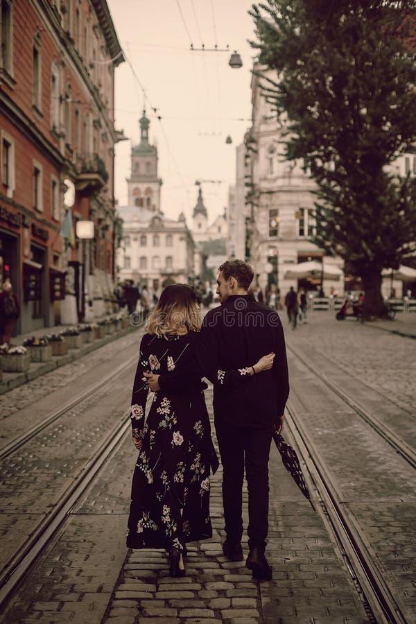 Coppie zingaresche alla moda nell'amore che cammina e che abbraccia nella città di sera fotografia stock libera da diritti