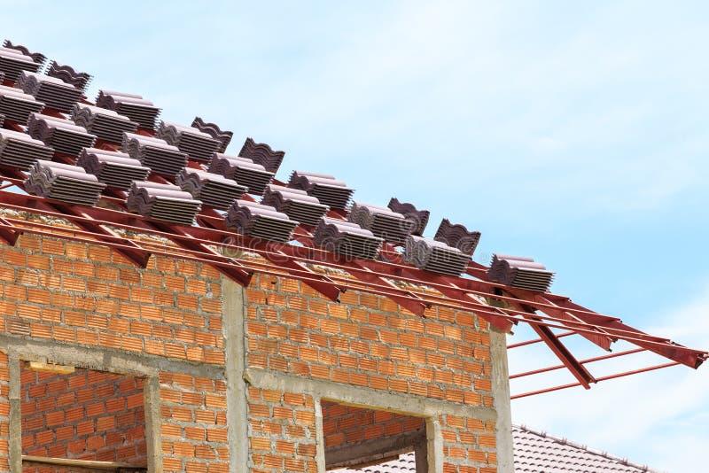 Copra in costruzione con le pile di mattonelle di tetto for Costruzione domestica economica