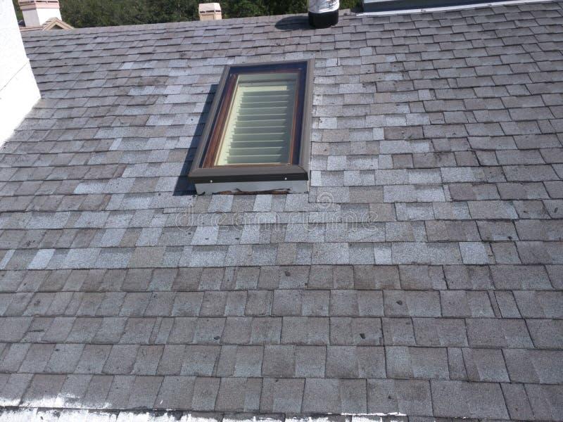 Copra le riparazioni della perdita e l'installazione del lucernario sul tetto residenziale dell'assicella immagine stock