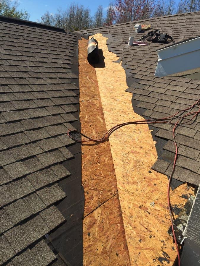 Copra le riparazioni della perdita sulla valle del tetto residenziale dell'assicella in lavorazione fotografia stock