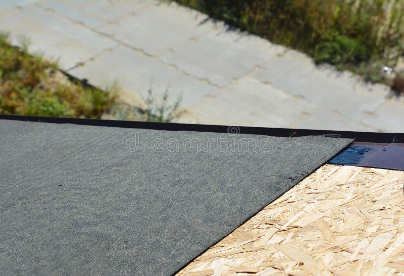 Coprendo costruzione con l'installazione delle assicelle dell'asfalto Preparazione della membrana della copertura sulla superfici immagine stock libera da diritti