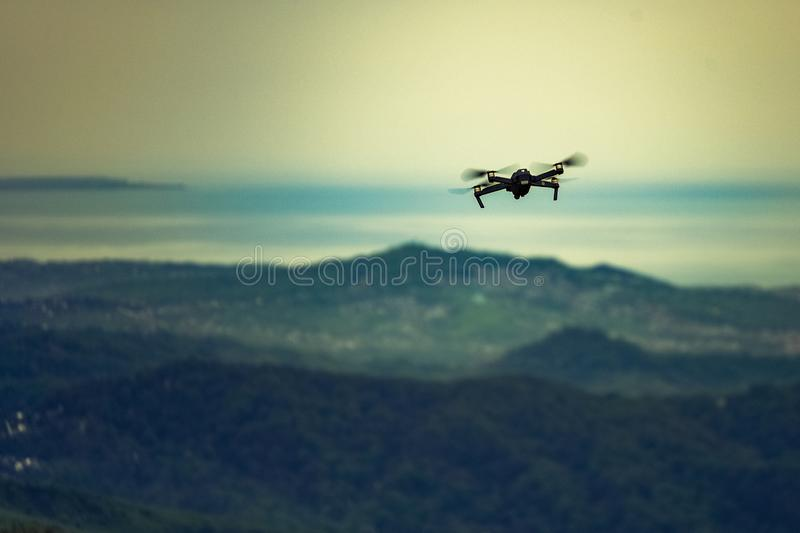 Copter in flight over the mountains on the horizon sea sunset royalty free stock images
