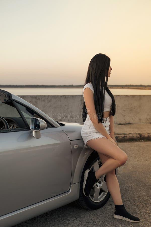 Copule magnifique de l'homme et de femme en voyage de voiture de vacances dans le jour d'été Voiture de sport grise de luxe femme photo stock