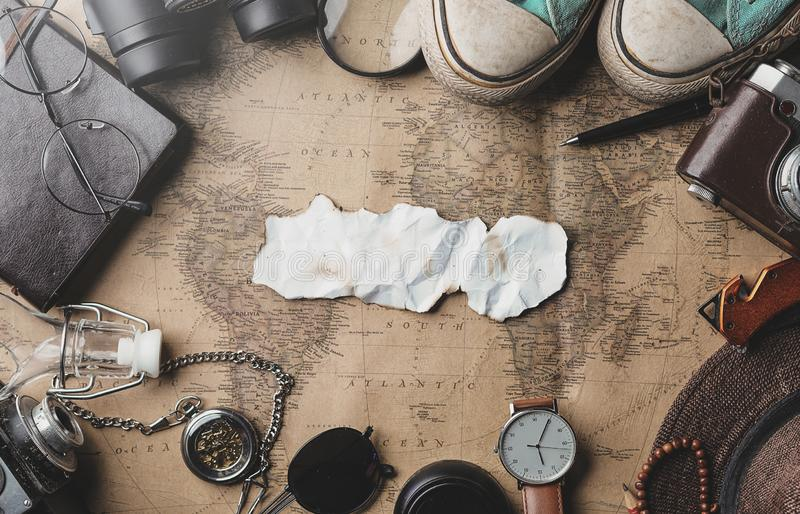 Copy Space of Burnt Paper Travel Concept Background. Overhead View of Traveler`s Accessories on Old Vintage Map royalty free stock image