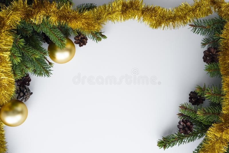Copy space for christmas wishes. Festive decorations such as gold baubles, tinsel, coniferous tree branches and cones. Christmas greeting card with copy space stock images