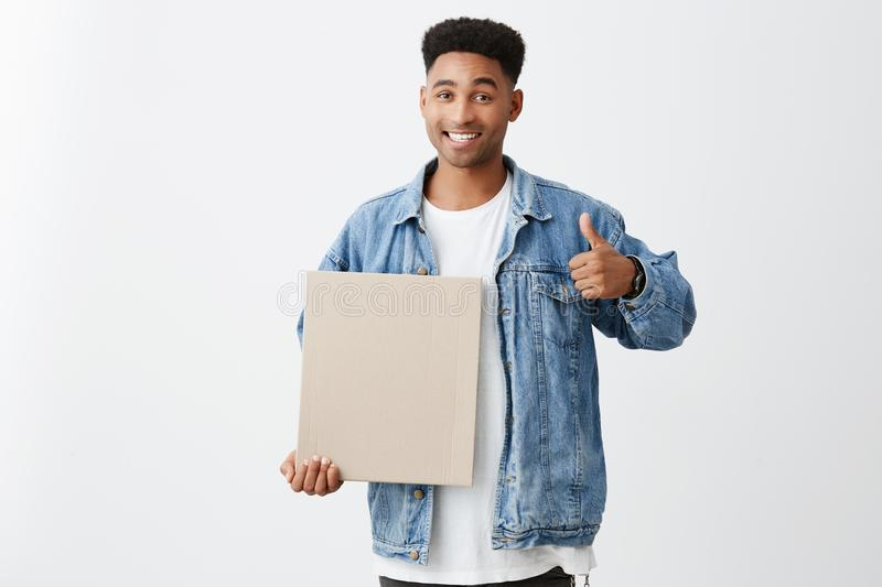 Copy space. Close up of cheerful young black-skinned male student with afro hairstyle in stylish casual outfit holding royalty free stock image