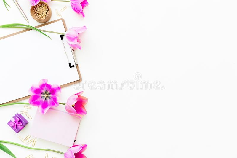 Copy space concept. Workspace with clipboard, notebook, pen, pink tulip flowers and accessories on white background. Flat lay, top stock photography