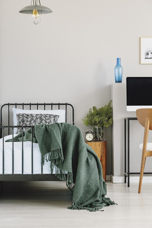 Copy space on empty grey wall of chic bedroom interior with industrial single bed with blue sheets, patterned pillow and dark. Green blanket royalty free stock photography