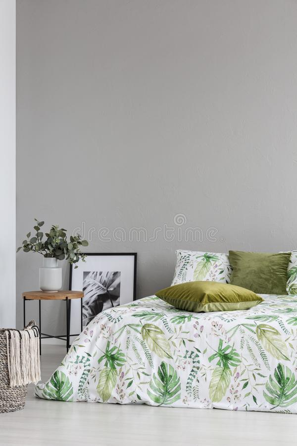 Copy space on the grey wall of cozy bedroom with leaf pattern on the bedding and olive green pillows stock image