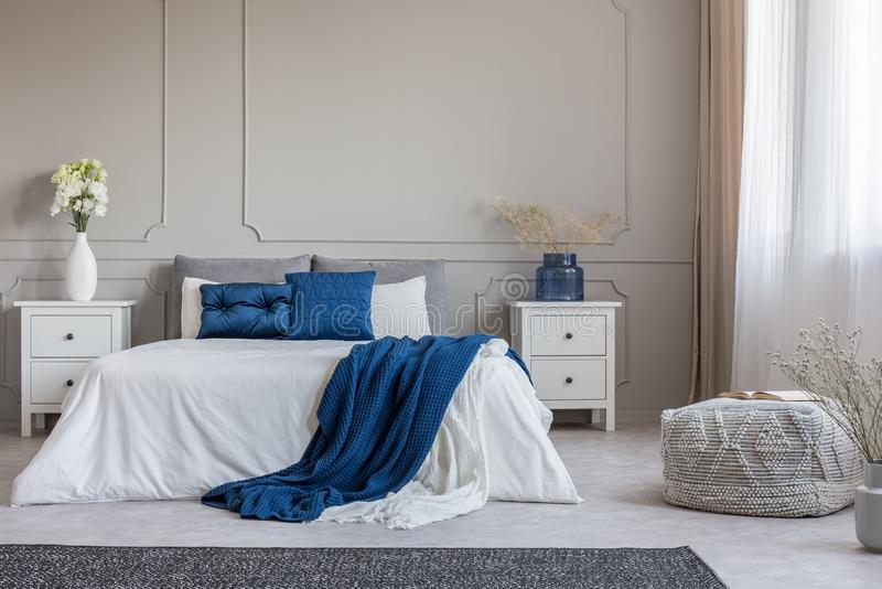 Copy space on empty grey wall of fashionable grey white and blue bedroom interior. Real photo concept royalty free stock photo
