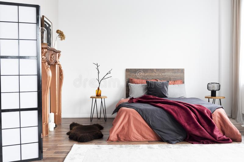 Copy space on empty white wall of rustic bedroom interior with king size bed with orange bedding and burgundy blanket. Copy space on empty white wall of rustic stock photos