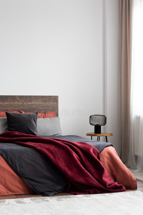 Burgundy Bedding And Gray Pillows On A Bed In A White Wall Bedroom Interior Real Photo Stock Image Image Of Interior Design 128408967