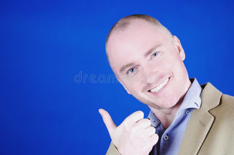 Copy space at his hand. Happy mature man in cream coat pointing copy space and smiling while standing against blue. Gesturing and signs concept. Copy space at royalty free stock photo