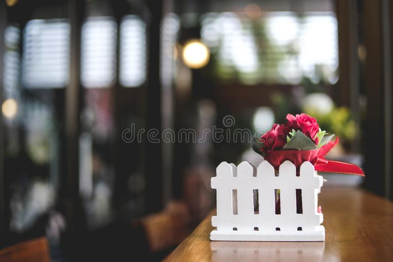 Copy space image artificial small red rose bouquet on wooden. Table of brown in blurred coffee cafe background, valentine concept royalty free stock photography