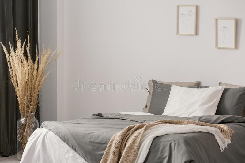 Copy space and posters on empty white wall of elegant bedroom interior with cozy king size bed. Copy space and posters on empty wall of elegant bedroom interior royalty free stock images
