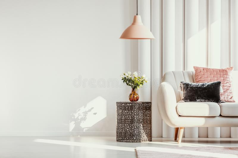 Copy space on white wall of elegant living room with white flowers on glass vase on stylish table next to white sofa. With pastel pink and black velvet pillows royalty free stock photography