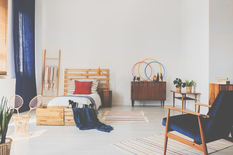 Copy space on the white wall of oldschool teenager bedroom with wooden furniture and dark blue accents royalty free stock image