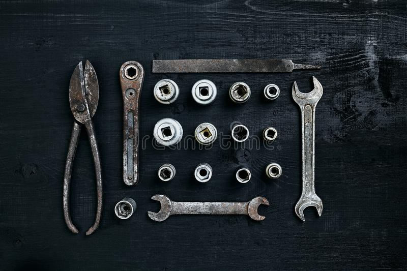Copy space of working tools on a black wooden surface. Nippers, wrench keys, pliers, screwdriver. Top view. Still life. Flat lay royalty free stock photo