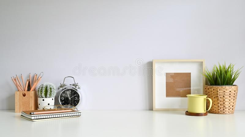 Copy space workspace with photo frame, coffee, plant decoration, pencil on office desk royalty free stock photography