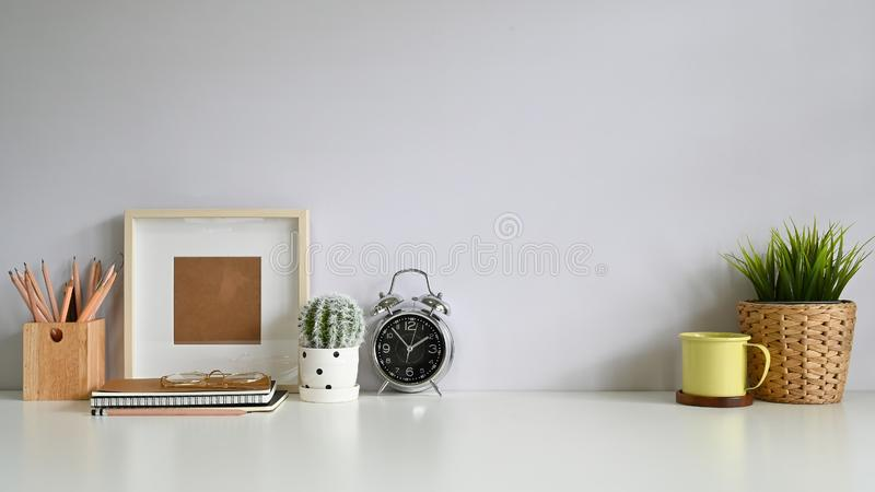 Copy space workspace with photo frame, coffee, plant decoration, pencil on office desk stock images