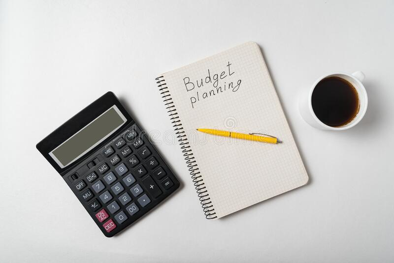 Copybook with Budget planning text. Notebook with calculator and cup of coffee on white background. Top view royalty free stock image