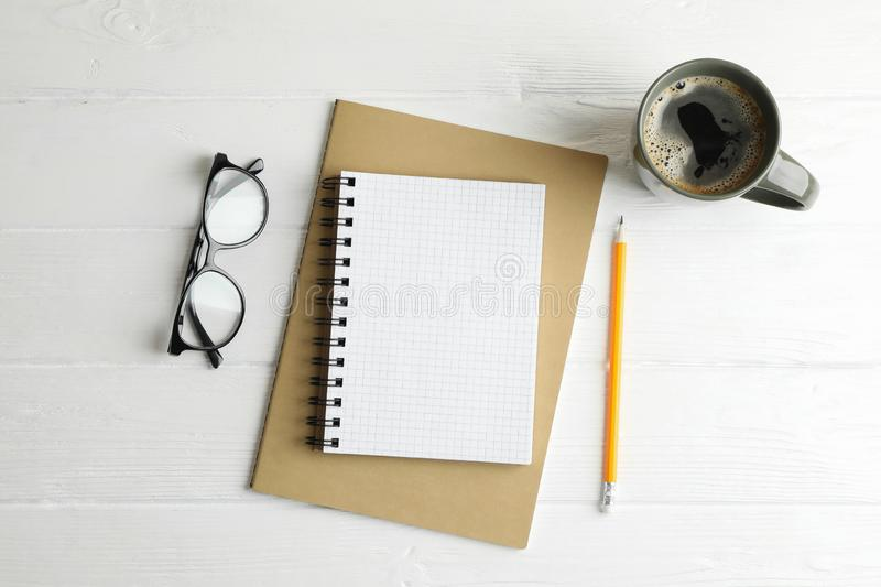 Copybooks, cup of coffee, pencils and glasses on wooden background royalty free stock photography