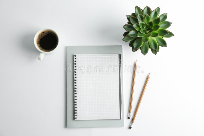 Copybooks, cup of coffee, pencils and succulent plant on white background stock photography