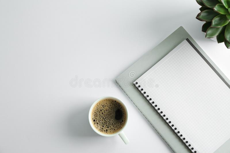 Copybooks, cup of coffee and succulent plant on white background stock images
