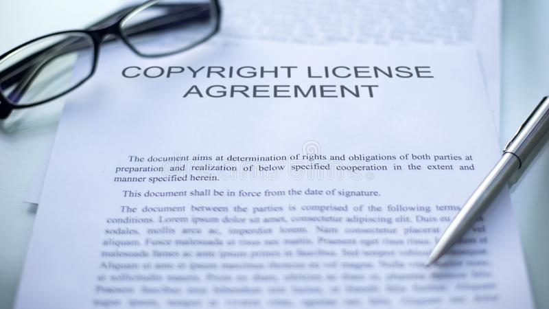 Copyright license agreement lying on table, pen and eyeglasses on document stock images