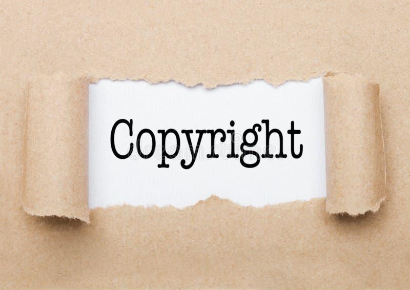 Copyright tekst pojawiać się za poszarpanym brown papierem obrazy stock