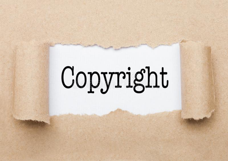 Copyright text appearing behind torn brown paper. Copyright concept text appearing behind torn brown paper envelope stock images