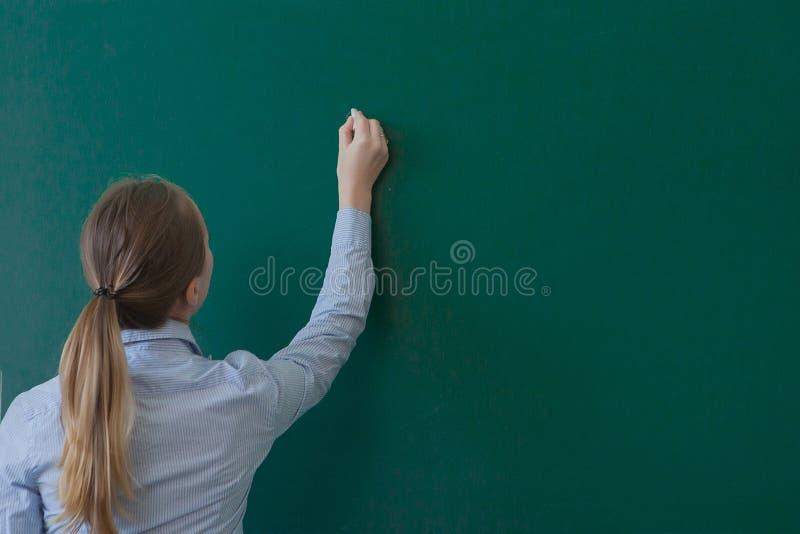 Вид сзади студента или учителя с длинным сочинительством волос брюнета на пустых зеленых классн классном или доске с copyspace стоковое изображение rf