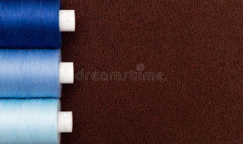 Copyspace auf braunem Gewebe mit Fadenspulen stockbild