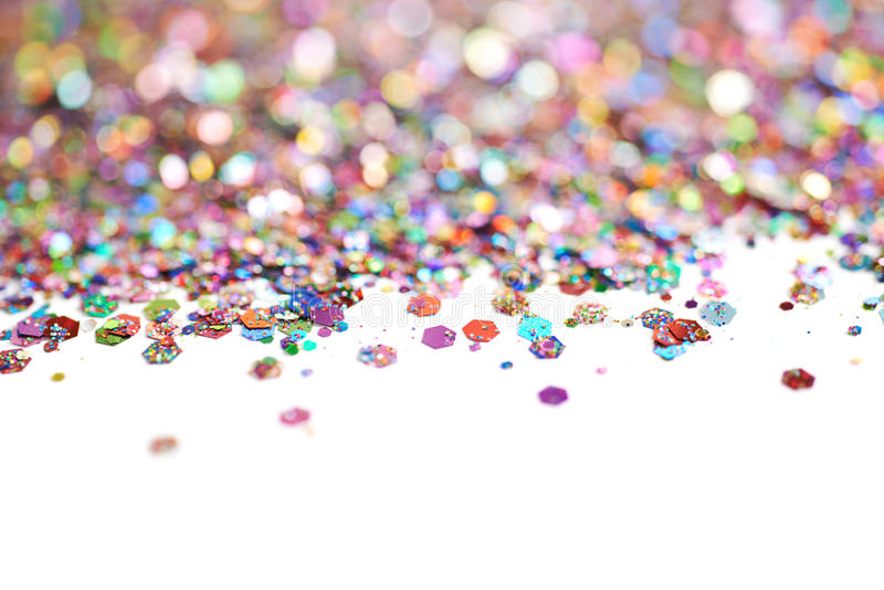 Copyspace backgdrop composition. Made of colorful and bright pile of sequins isolated over the white background royalty free stock photo
