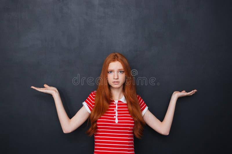 Copyspace confuso della tenuta della donna su entrambe le palme sopra il fondo della lavagna immagini stock