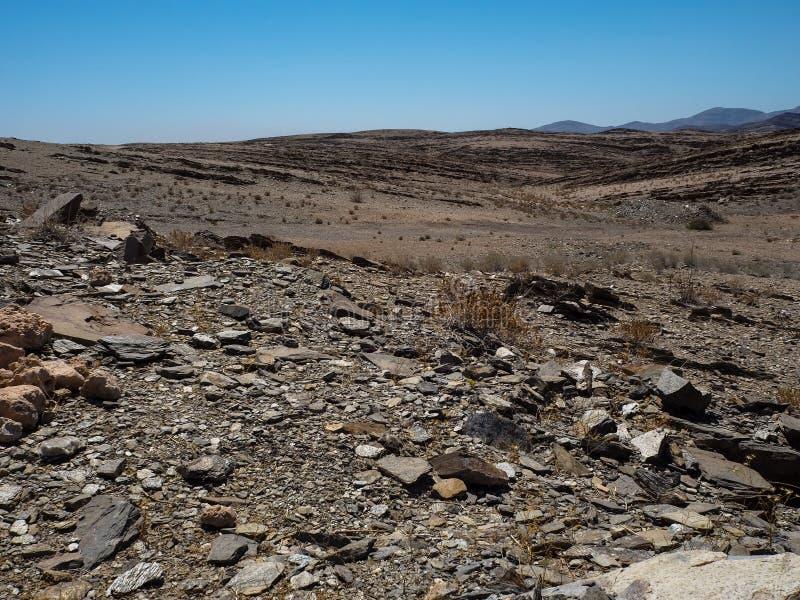 Copyspace des harten Lebens Felsenberg zeigend trocknete staubigen Landschaftsboden von Namibischer Wüste mit Spaltungsschieferst stockfoto