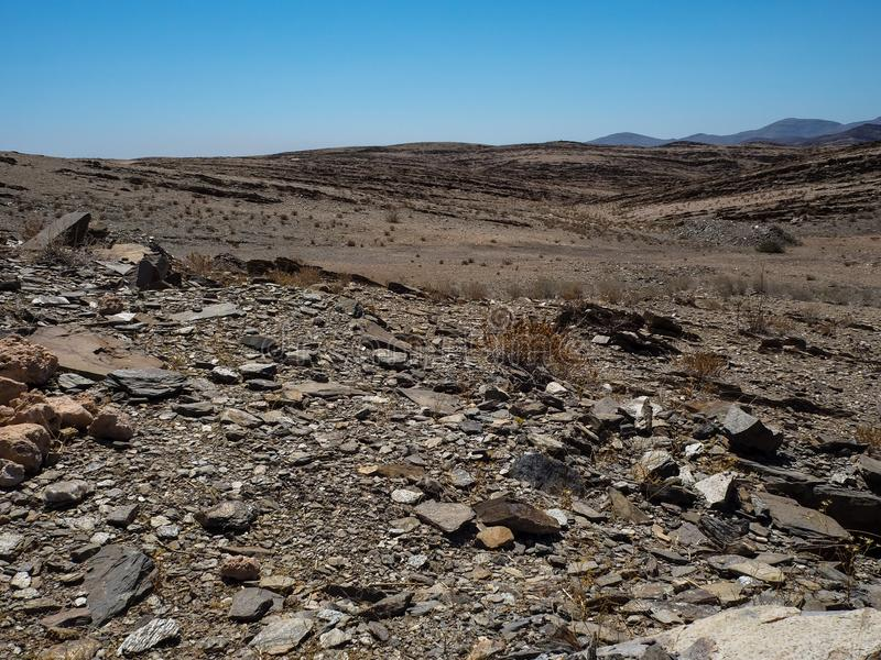 Copyspace of hard life showing rock mountain dried dusty landscape ground of Namib desert with splitting shale pieces. Other stone, desert plant and blue sky stock photo