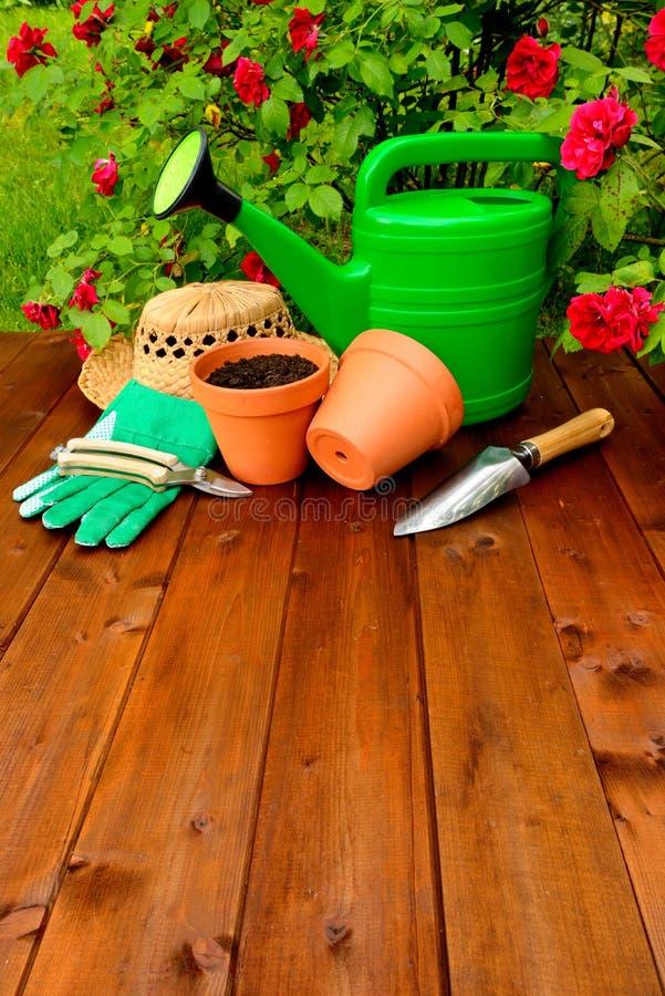 Copyspace het tuinieren de hulpmiddelen op houten lijst en namen bloemenachtergrond toe stock afbeelding