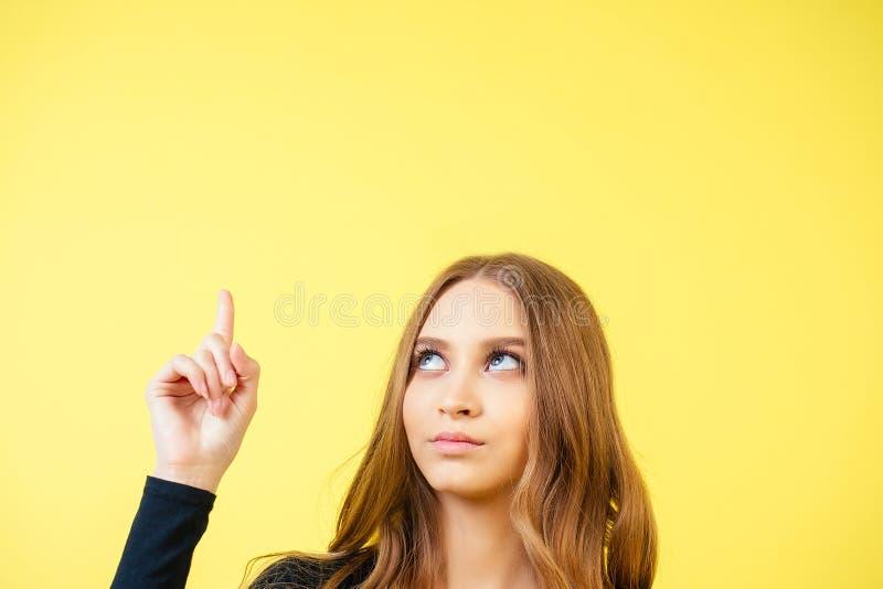 Copyspace-Porträt einer jungen, attraktiven cleveren Frau mit Schminkspitzen Finger auf den oben im Studio auf einem gelben stockbild