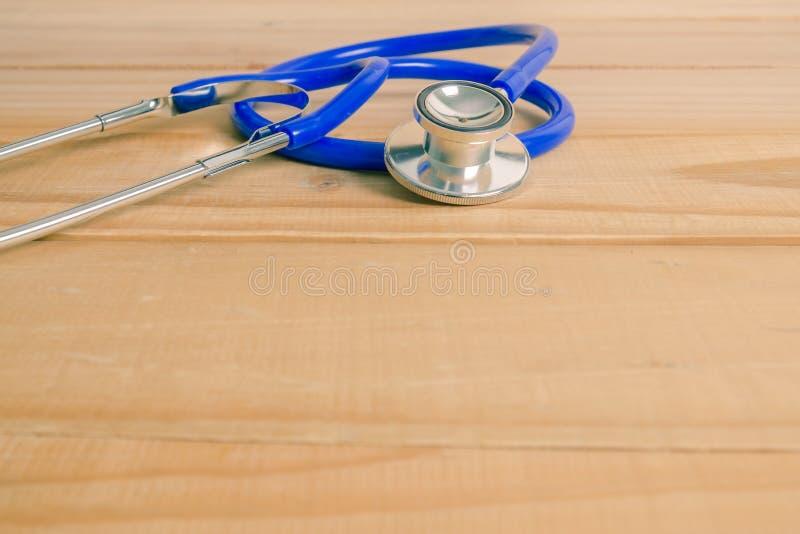 Copyspace: Stethoskop eines Doktors auf hölzernem Hintergrund lizenzfreie stockfotografie