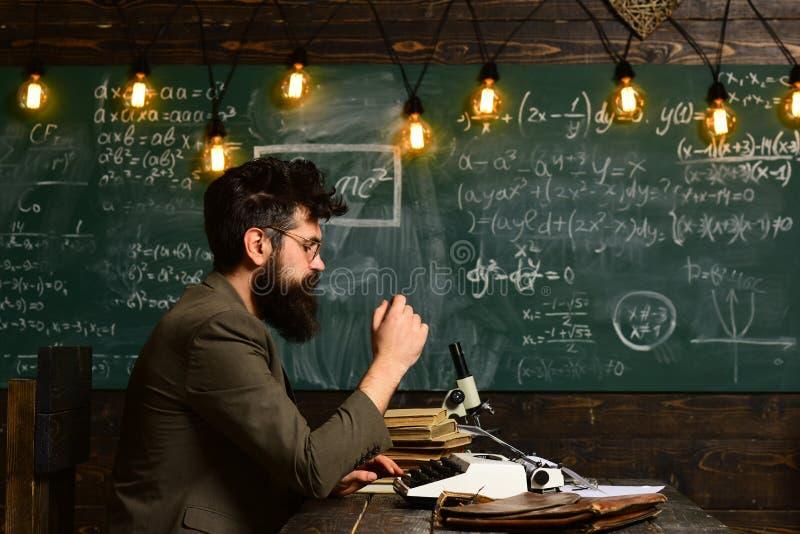 Copywriter blogger, dziennikarza modnisia mężczyzna tworzy zawartość z brodą i szkła pisać na maszynie na maszyna do pisania, pis zdjęcia royalty free